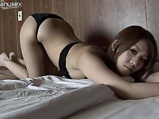 Eye catching Asian seductress lies on the bed wearing bikini